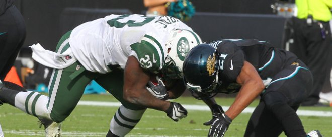New York Jets running back Shonn Greene (23) lowers his head as he runs into Jacksonville Jaguars cornerback Derek Cox (21) during an NFL game on December 9, 2012. The Jets defeated the Jaguars 17-10. (AP Photo/Kevin Terrell)